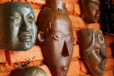 Wooden Mayan masks on display  and for sale  on a brick wall in an indoor market in Mazatlan, Mexico