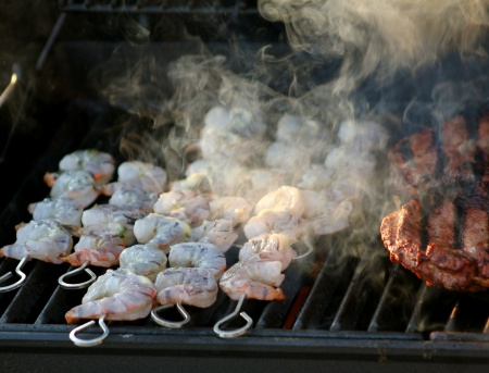 Skewered shrimp cooking  and smoking  on a barbecue grill along side beef