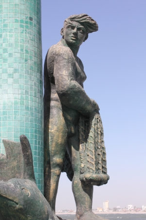 A fountain featuring a bronze fisherman statue with Old Mazatlan in the background