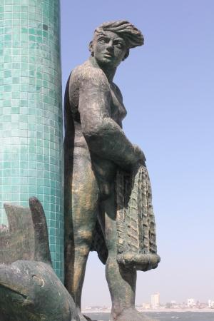 Uma fonte com uma estátua de bronze com pescador Old Mazatlan em segundo plano Imagens
