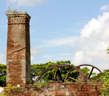 Ruins of an abandoned and overgrown sugar mill in Cuba on a sunny day