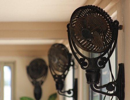 Three vintage fans mounted near the ceiling to provide a breeze in a very large room