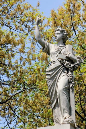 A stone statue of a barefoot woman pointing upward and holding a large crucifix and floral wreath, on a tomb at Graceland Cemetery, Chicago, Illinois, USA Stock Photo