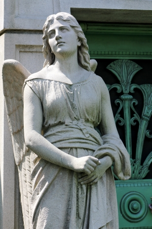 A stone statue of a young female angel guards the green weathered door to a mausoleum at Graceland Cemetery, Chicago, Illinois, USA
