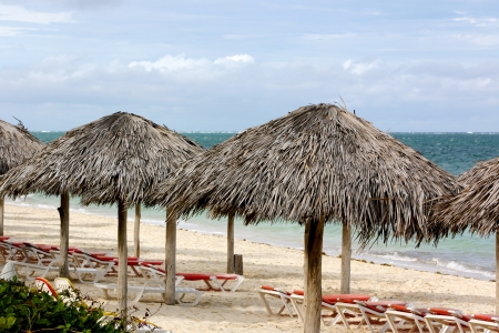 Straw beach umbrellas and lounge chairs on a deserted beach on a dark and windy day