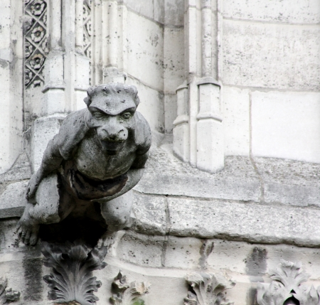 A lone, outstretched stone gargoyle appears to be soaring straight out from Notre Dame Cathedral, Paris, France