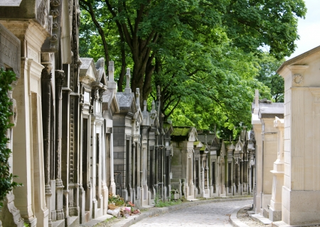 Aged and weathered mausoleums lining both sides of a path in Pere Lachaise Cemetery, Paris, France