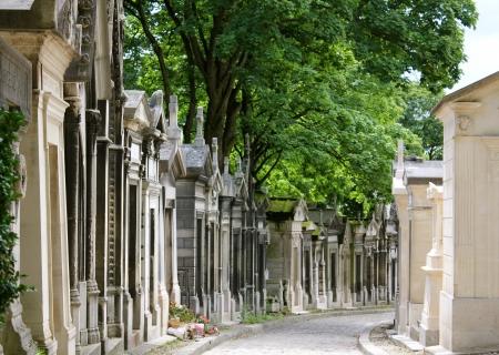 Mausoléus envelhecido e resistiu alinham ambos os lados de um caminho em Pere Lachaise, em Paris, França