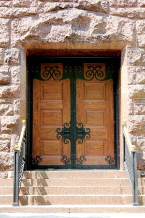Escadas que conduzem para portas de madeira com elementos de ferro forjado, em um bloco de constru