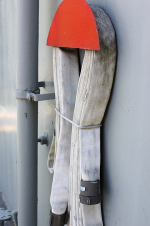 A fabric fire hose looped and stored on the wall of a ship