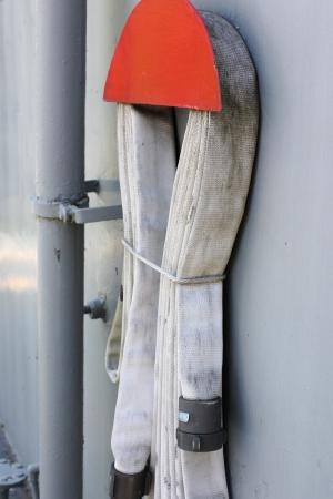 Uma mangueira de incêndio tecido enrolado e armazenado na parede de um navio Imagens