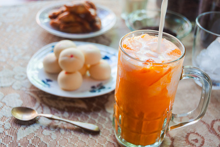 Cha Thai, Thai iced tea pouring milk on top with plate of thai mochi sweet dessert on the table, selective focus Stock Photo