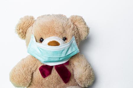 可爱的泰迪熊与面具在他的嘴在白色的背景