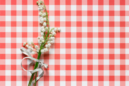 Lilly of valley on red and white checked pattern background
