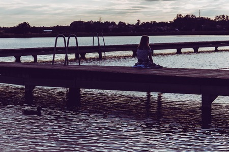 Young female girl sitting on wooden pier looking at the water Banque d'images