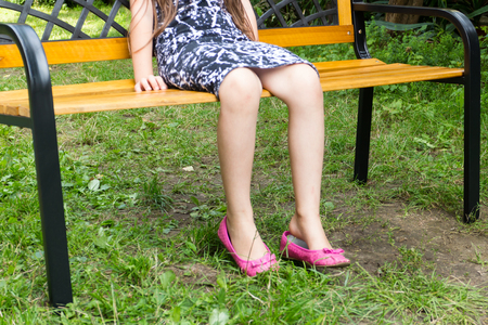 One girl sitting alone on bench waiting Stock Photo