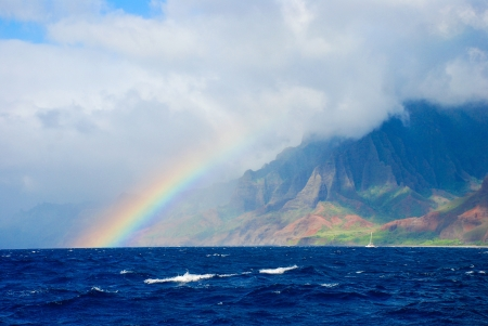 rainbow and storm over the Napali Coast with deep blue ocean and warm afternoon light over the mountains