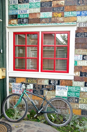 Green bike against wall decorated with old licesne plates anmd a red window pane.