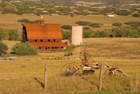farm equipment: Historic brown barn, silo, and farm equipment photographed in morning light