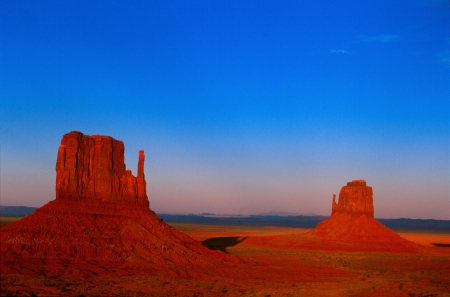 colrful: Last rays of light illuminate the Mittens at Monument Valley National Monument Stock Photo