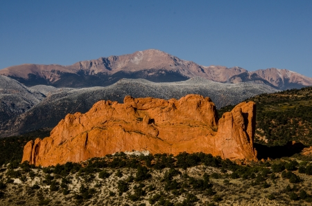 Warm light in the early morning illuniates the Kissing Camels monolith and Pikes Peak in Colorado Springs, Colorado