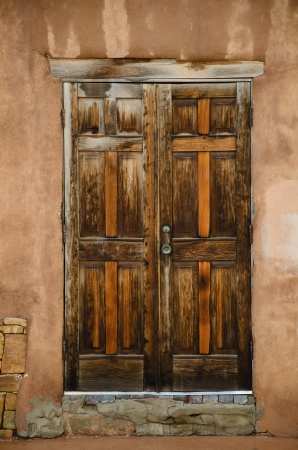 adds: A morning rainstorm adds texture on an old building with two weathered wooden doors in downtown Santa Fe, New Mexico