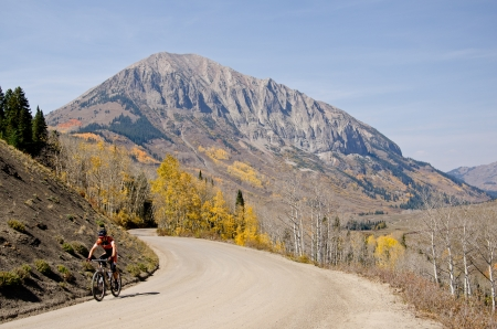 A mountian biker on picturesque Gothic Road in with fall colors and Gothic Mountain in the background