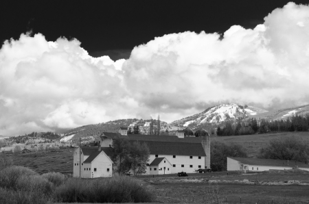 sweeps: A dramtic May storm sweeps over the Waatch Mountian and a classic white barn near PArk CIty, Utah  Editorial