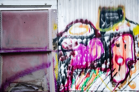 compostion: Colorful grafitti and paint and a window on an old warehouse in downtown Colorado Springs by the railroad tracks