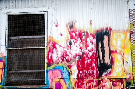 compostion: Colorful paint and grafitti on the white wall of an old warehouse by the traintacks in downtown Colorado Springs, Colorado