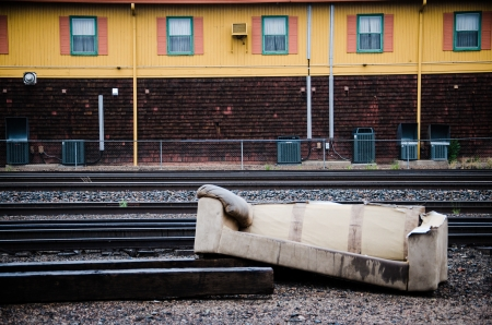 dumped: An old couch that was previously used by homeless indiduals was dumped next to railroad traks in downtown Colorado Springs  Editorial