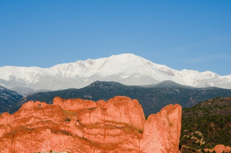A close-up view of the iconic Kissing Camels in Garden of the Gods Park with snow-capped Pikes Peak in the background the morning after a May storm - Colorado Springs, Colorado
