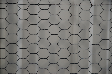 Abstract pattern sin chicken wire taken outside of a metal barn
