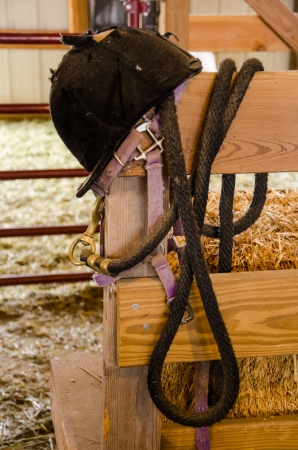 Riding hat and bridle hanging on fence in barn