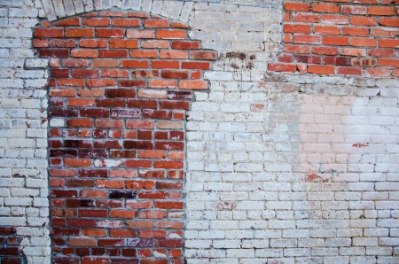 compostion: Downtown alley with wall of red brick and faded white paint which is am popular spot for portraits