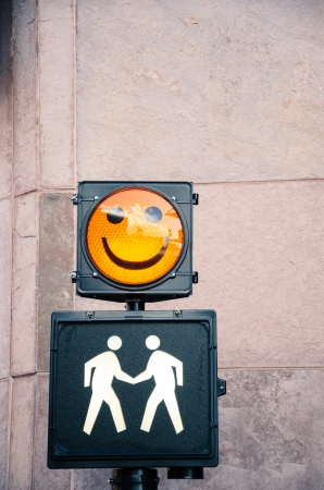 A crossing sign in downtown Colorado Springs with a happy face and figures shaking hands.