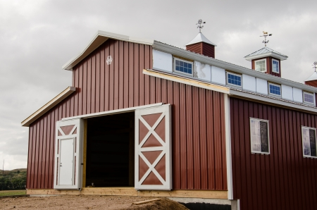 large doors: Large red modern barn and storm clouds and open doors