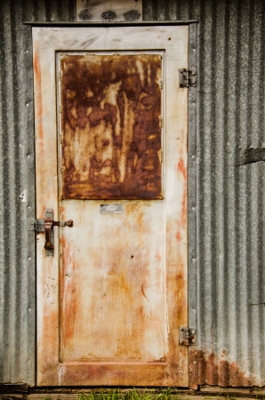 puerta de metal: Puerta de metal oxidado y la pared exterior de metal en granja local