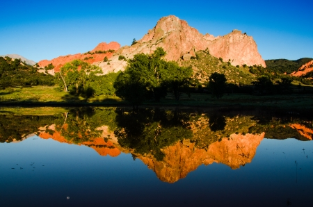 The dramatic red rock monoliths of Garden of the Gods reflect in the Valley Reservoir on a clear morning with blue sky and moon reflection