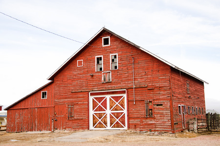 A classic red barn with white trim in good condition on the Colorado plains in afternoon light