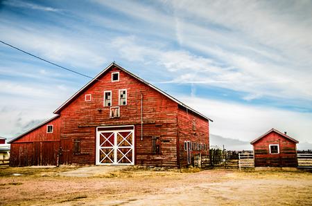 Un granero rojo clásico con toques blancos en las llanuras de Colorado establece agianst un cielo parcialmente nublado y azul