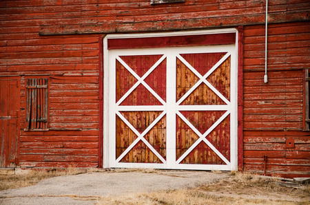 A wooden red barn door with white trim in late afternoon light in Colorado