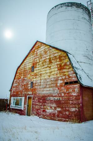 breaking out: Granero cl�sico y el silo con el sol que se rompe a cabo despu�s de la tormenta de nieve fresca en Falcon, Colorado en un hermoso d�a de febrero Editorial