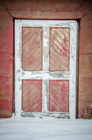 white trim: Door of weathered, red barn with white trim after fresh snow storm Stock Photo