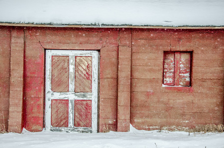 white trim: Outer wall and door of weathered, red barn with white trim after fresh snow storm