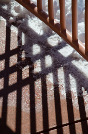 Abstract pattern of dark shadows created by rails at Manitou CLiff Dwellings near Colorado Springs on a sunny February morning.