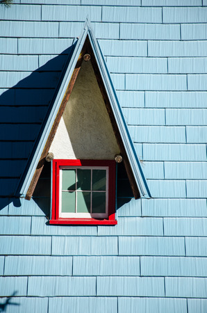 Blue shingles and red-trimmed window on building in Christmas village of North Pole, Santas Worksop, Cascade Colorado.