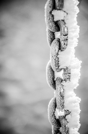 compostion: Swing chain covered with frezzing drizzle  rime ice  on a neighborhood playground on a frozen, foggy morning Stock Photo