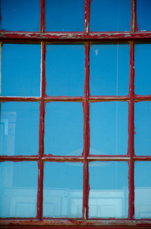 faded: Window in old building  with faded and chipped red paint on pane that creates geometric pattern and reflects blue sky.