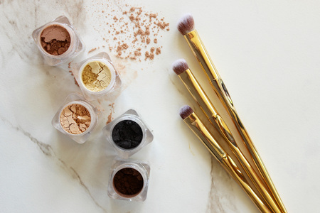 Loose eyeshadow in containers with gold brushes. White marble copy space. 免版税图像
